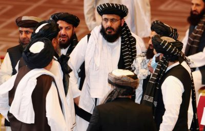 Taliban delegates speak during talks between the Afghan government and Taliban insurgents in Doha, Qatar, 12 September 2020 (Photo: Reuters/Ibraheem al Omari).