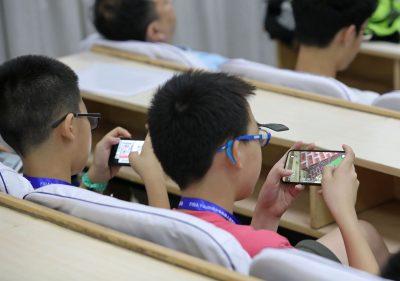 2018年7月17日、中国中部河南省鄭州市で小学生がスマートフォンにビデオゲームをしている(写真:ロイター)。