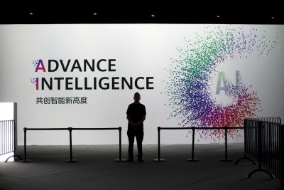 A security officer keeps watch in front of an AI (Artificial Intelligence) sign at the annual Huawei Connect event in Shanghai, China, 18 September 2019 (Photo: Reuters/Aly Song).