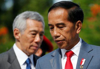 Presiden Indonesia Joko Widodo memeriksa seorang penjaga kehormatan di Istana di Singapura bersama Perdana Menteri Singapura Lee Hsien Loong pada 8 Oktober 2019 (Foto: Reuters / Feline Lim).