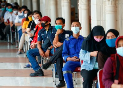 People wearing protective masks sit as they queue before receiving a dose of China's Sinovac Biotech vaccine for the coronavirus disease (COVID-19) at the Tanah Abang textile market, as Indonesia drives mass vaccination for vendors in Jakarta, Indonesia, February 17, 2021 (Photo: Reuters/Ajeng Dinar Ulfiana).