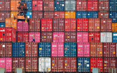 A worker walks on stacks of containers at the Tanjung Priok port in Jakarta, Indonesia, 22 January 2021 (Photo: Reuters/Ajeng Dinar Ulfiana).
