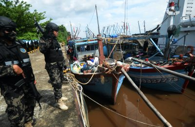 Two Indonesian officers stand near a vessel from Vietnam which is secured at the Pier of the Pontianak Fishery and Marine Resources Monitoring Station in Kubu Raya Regency, West Kalimantan Province, Indonesia, 12 April, 2021 (Photo: Arief Nugroho/Opn Images/Cover Images via Reuters).