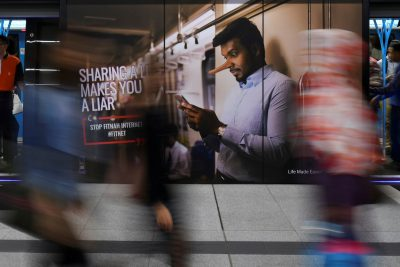 Commuters walk past an advertisement discouraging the dissemination of fake news at a train station in Kuala Lumpur, Malaysia, 28 March 2018 (Photo: Reuters/Stringer).