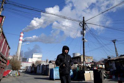 A man walks near a coal-fired power plant in Harbin, China, 27 November 2019 (Photo: Reuters/Jason Lee).
