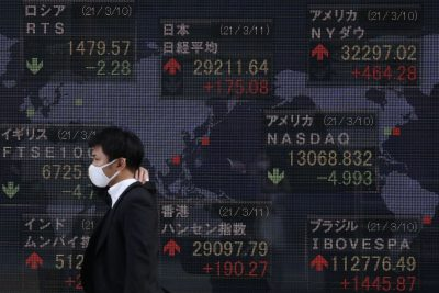 A man wearing a face mask walks past an electronic board showing currency exchange rates at a securities firm in Tokyo, March 2021 (Photo: James Matsumoto/SOPA Images/Sipa USA via Reuters)