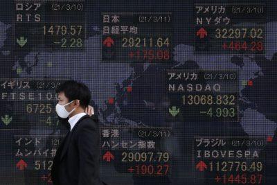 마스크를 쓴 남성이 2021 년 3 월 도쿄의 한 증권사에서 환율이 표시된 전자 판을 지나가고있다 (사진 : James Matsumoto / SOPA Images / Sipa USA via Reuters)