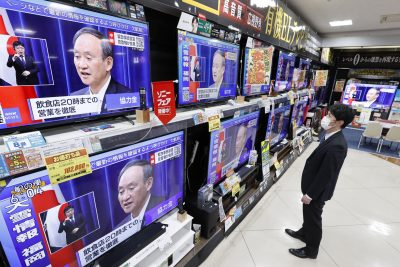 TV screens at an electronics store in Fukuoka, southwestern Japan, show Prime Minister Yoshihide Suga speaking at a press conference on 7 January 2021 (Photo: Kyodo via Reuters).