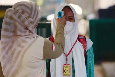 Seorang siswa sekolah dasar bertopeng memeriksa suhu tubuhnya sebelum menghadiri sesi kelas ketika sekolah dibuka kembali antara COVID-19 di Pegasi, pinggiran Jakarta, pada 24 Maret 2021 (Foto: Reuters / Willie Guernian).