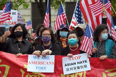 People holding American flags and anti-hate signs, New York, 2 May 2021 (Photo: Reuters/Anthony Behar).