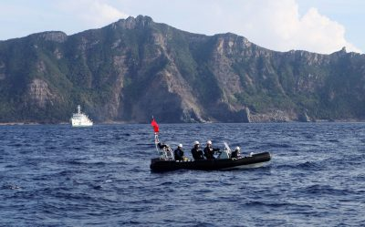 A Japan Coast Guard boat and vessel sail past one of the disputed Senkaku/Diaoyu islands, 18 August 2013 (Photo: Reuters/Ruairidh Villar).