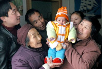 Parents, grandparents and a great-grandmother carry a baby to a home in Yangguidian village, Hubei province, February 9, 2005 (Photo: Reuters).