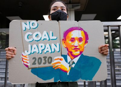 A young climate activist holds a banner during a rally calling on policy makers to raise the target of greenhouse gas reduction outside the Ministry of Economy, Trade and Industry, to mark the World Earth Day in Tokyo, Japan 22 April 2021 (Photo: Reuters/Androniki Christodoulou).