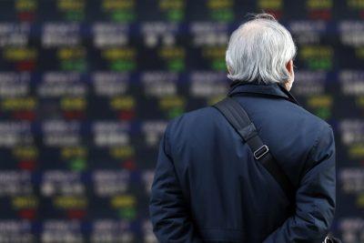 A man walks past a sign showing exchange rates, Tokyo, March 12, 2021 (Photo: Reuters / James Matsumoto)