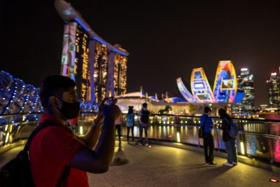A man stands outside Marina Bay Sands with his smartphone in Singapore on February 24, 2021 (Photo: Maverick Asio / SOPA Images / Sipa via Reuters Connect).