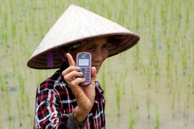 A farmer shows her Nokia cell phone on a rice pady outside Hanoi, Vietnam, 13 July 2017 (Photo: Reuters/Kham)