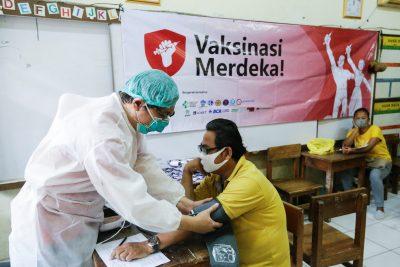 Seorang petugas kesehatan menguji seorang pria untuk vaksin virus corona (Govit-19) selama program vaksinasi pada 17 Agustus 2021 di Jakarta, Indonesia.