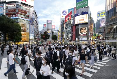 People wearing masks for protection against the coronavirus walk across a scramble intersection in Tokyo's Shibuya area, 20 August 2021 (Photo: Reuters).