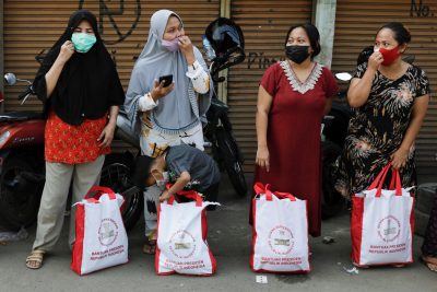 Wanita mengenakan masker pelindung untuk mencegah penyebaran Kovit-19 berdiri di sebuah jalan di Jakarta, Indonesia pada 16 Juli 2021 setelah menerima bantuan dari Presiden Indonesia (Foto: Reuters / Willie Kourniavan).