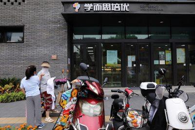 2021年7月26日、中国の北京にあるTAL Education Groupが所有する特殊教育サービスプロバイダーであるXueersiの店舗の前にいる大人と少女(写真:Tingshu Wang / Reuters)。