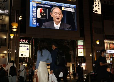 Japanese Prime Minister Yoshihide Suga makes an announcement on a large screen in Tokyo, 9 September 2021 (Photo: Yoshio Tsunoda/AFLO via Reuters).