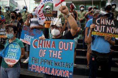 Activistas organizan una protesta frente al consulado chino, custodiada por la policía filipina, en el quinto aniversario del fallo de la Corte Internacional de Arbitraje que invalida los reclamos históricos de Beijing sobre las aguas del Mar de China Meridional, en Makati, Filipinas, el 12 de julio de 2021. REUTERS / Eluisa López
