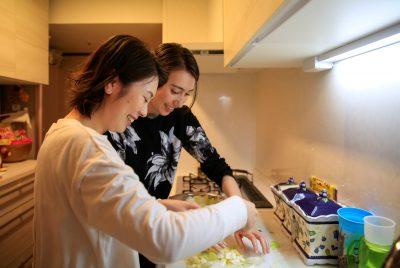レズビアンのカップルであるジェニーと鳴海は2021年3月19日、日本の東京にあるジェニーの両親の家で一緒に料理をしている(Photo:Akira Tomoshige / Reuters)。